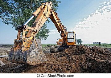 excavator digs a hole - excavator digging a trench for the...
