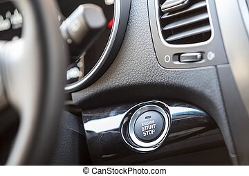 Car interior, engine start button under the steering wheel