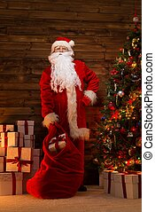 Santa Claus in wooden home interior with sack full of...