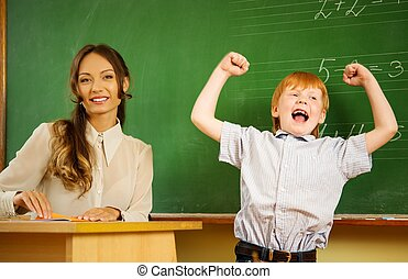 Little happy redhead boy answering near blackboard in school...
