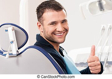 Smiling young man at dentists surgery with thumb up