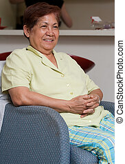 Relaxing at home - Senior asian woman sitting on a chair...