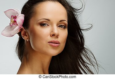 Young beautiful brunette woman with orchid flower in her waving hair