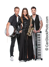 Stylish sexy band posing together with music instruments. Two men with drum and piano and beautiful sexy girl in black dress with sax