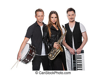 Sexy fashionable jazz band posing on camera. Standing with music instruments isolated over white background.