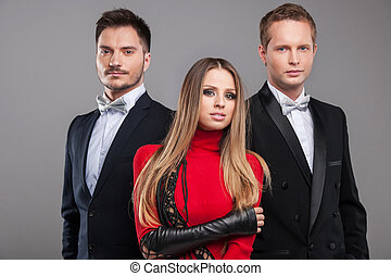 Sexy posing of one female blond model and two male models. Looking at camera and standing isolated over grey background