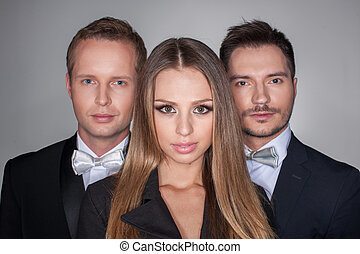 Portrait of three attractive people isolated over grey background. Sexy blond girl standing on foreground and stylish men in the same classical suites on background