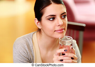 Young beautiful pensive woman holding glass with water at...