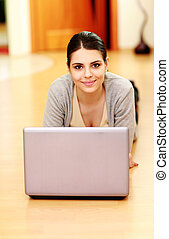 Young beautiful woman lying on the floor with laptop
