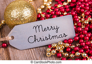 A metal tag wishing a Merry Christmas surrounded by Christmas decorations