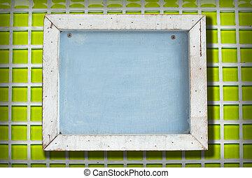 Blank chalkboard in wooden frame on ceramics. wall...