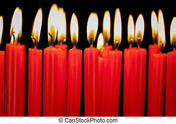 Burning candles in a row on black background