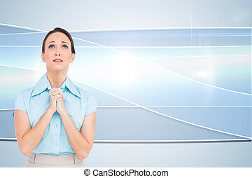 Composite image of troubled young businesswoman praying...