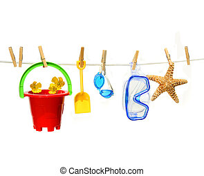 Childs summer toys on clothesline against white background