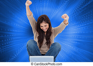 Composite image of brunette cheering while using laptop -...