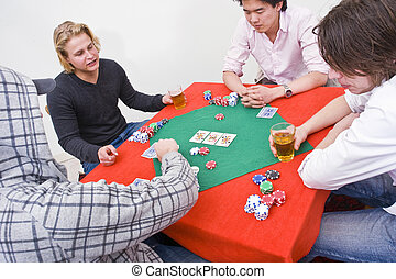 Poker game - Four people around a table during a poker game