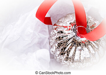 antique glass Christmas tree baubles wrapped in protective tissue, and threaded on to a red satin ribbon. Space for your text