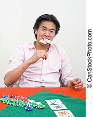 Poker frustration - A frustrated poker player biting his...