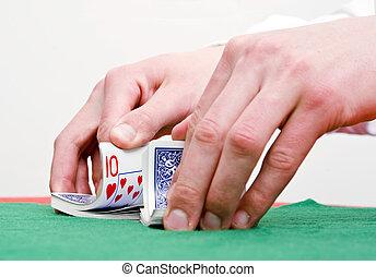 Shuffling cards - Dealer\'s hands shuffling cards during a...