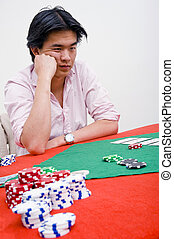 Bad hand - An Asian poker player being unhappy after losing...