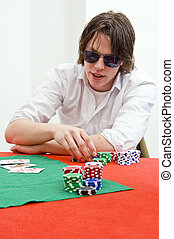 Poker Player - A man, wearing large sunglasses, playing a...