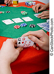 Peeking at the cards - A poker player taking a peek at his...