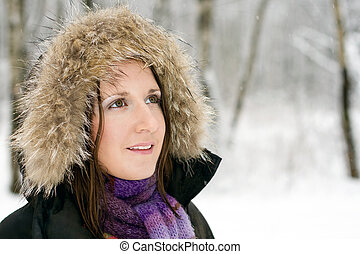 Woman in forest with fur hood and snow on it