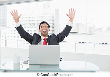 Businessman cheering in front of laptop at office desk -...