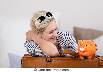 Trendy traveler with a piggy bank - Trendy beautiful young...