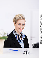 Beautiful hotel receptionist at the counter - Beautiful...