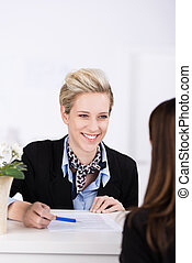 Welcoming hotel receptionist smiling at a guest - Welcoming...