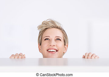Joyful young woman - Joyful young blond woman peering over...