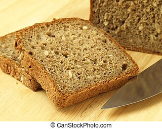 Slices of bread - Two slices of wholemeal bread on cutting...