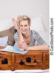 Smiling beautiful woman planning her holidays lying relaxing...