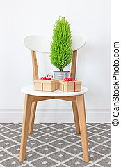 Presents and little green tree on a white chair