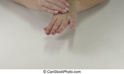 Applying cream to hands - A woman applying cream to hands