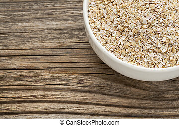 oat bran - a ceramic bowl on grained wood background