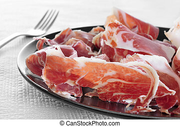 spanish serrano ham served as tapas - a plate with spanish...