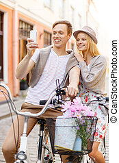 couple with bicycles and smartphone in the city - summer...