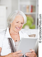 Senior woman reading an e-book on a tablet - Senior woman...