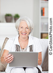 Happy senior lady using a laptop computer