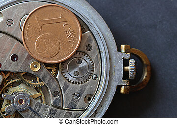 Money mechanism - European one cent coin lying on watch...