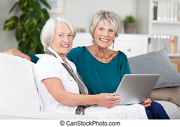Two elderly ladies sharing a laptop computer as they relax...