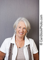 Beautiful stylish senior woman standing against a dark grey...