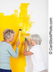 Two women having fun painting a wall - Two senior women...