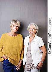 Two beautiful happy senior women with a relaxed optimistic...