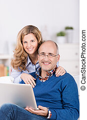 Smiling affectionate couple using a laptop with the wife...
