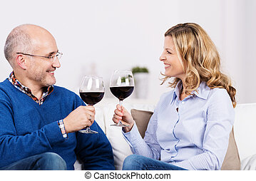 Attractive couple celebrating over a glass of wine sitting...