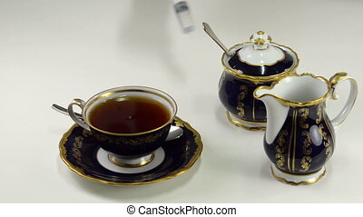 Poison into tea cup - Someone makes a lethal injection into...