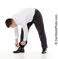 Man bending down to do up his shoelaces - Supple businessman...